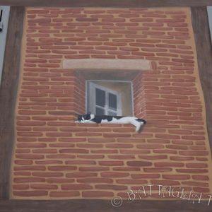 Une fenêtre en trompe-l'œil accueille la sieste de Pomponette, la chatte du boulanger