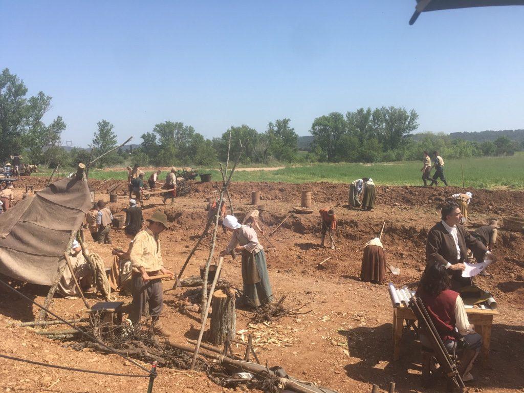 Scène de tournage du chantier en costumes d'époque.